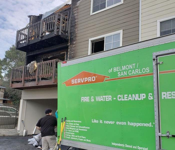 SERVPRO vehicle parked in front of home with fire damage